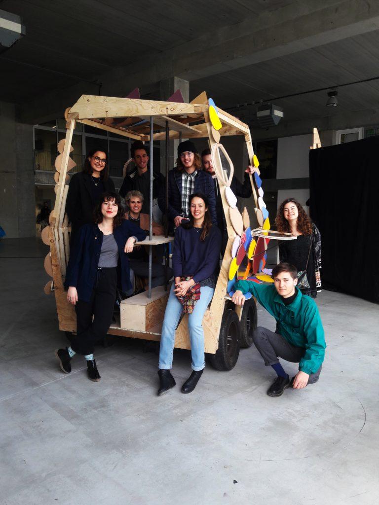 Les étudiant·es architectes posent dans le premier prototype à l'échelle d'un maillon du serpent, petite voiture en bois avec des décorations colorées faites de différents matériaux.